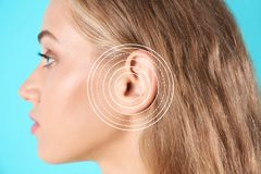 Young woman with symptom of hearing loss. On color background. Medical test stock images