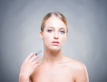 Young woman with syringe injecting botox into smooth skin Stock Photos