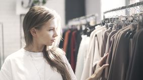 Young woman in a T shirt is choosing clothes in a store. Beautiful young woman wearing a white T shirt is passing by racks of clothes a store trying to find what stock video