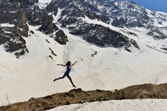 Young woman in t-shirt among snowy mountains stock image