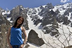 Young woman in t-shirt among snowy mountains royalty free stock photography
