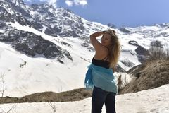 Young woman in t-shirt among snowy mountains stock photo