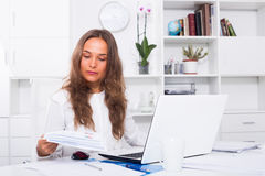 Young woman at the table in office Royalty Free Stock Image