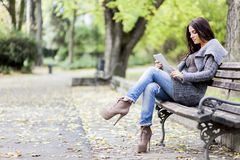 Young woman with tablet on the bench Stock Images