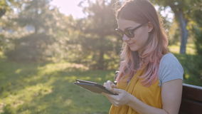 Young woman with tablet on the bench stock footage