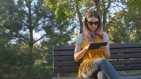 Young woman with tablet on the bench stock video
