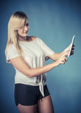 Young woman with tablet on blue Stock Images