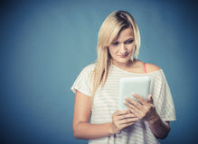 Young woman with tablet on blue Royalty Free Stock Photography