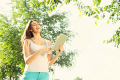 Young woman with tablet and coffee in park laughing Royalty Free Stock Image