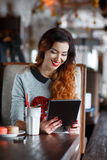 Young woman with tablet computer in cafe Stock Photography