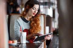 Young woman with tablet computer in cafe. A bright ,beautiful woman with curly red hair,red lipstick,beautiful makeup,red nail Polish,sitting alone at a table in royalty free stock photo