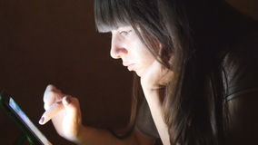 Young woman with tablet computer lying on sofa. Girl using tablet computer at home late night. Glowing light on face stock video