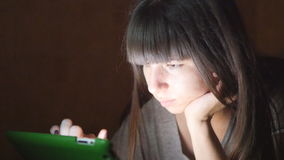 Young woman with tablet computer lying on sofa. Girl using tablet computer at home late night. Glowing light on face. She uses mobile device to shopping online stock video footage