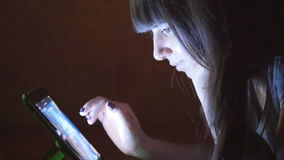 Young woman with tablet computer lying on sofa. Girl using tablet computer at home late night. Glowing light on face. She uses mobile device to shopping online stock footage