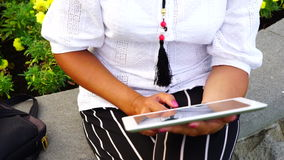 Young woman with tablet computer sitting in city park stock footage
