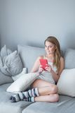 Young Woman with Tablet Computer Sitting on Sofa Royalty Free Stock Photography