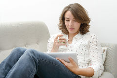 Young woman with a tablet drinks a cup of tea Stock Photo