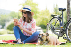 Young woman with tablet and her puppy Stock Photography