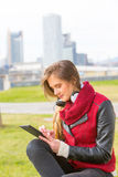 Young woman with tablet informing. Girl sitting with their tablet line and the city with its skyscrapers Stock Photos