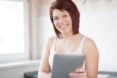 Young Woman with Tablet PC. Young woman with tablet in kitchen stock photography