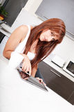 Young woman with a Tablet PC in the Kitchen Royalty Free Stock Photography