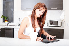 Young woman with a Tablet PC in the Kitchen Stock Images