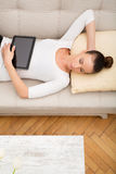 Young woman with a Tablet PC on the Sofa Royalty Free Stock Photos