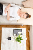 Young woman with a Tablet PC on the Sofa Royalty Free Stock Image