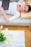 Young woman with a Tablet PC on the Sofa Royalty Free Stock Photo