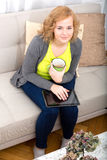 Young woman with a Tablet PC on the Sofa Stock Images