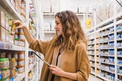 Young woman with a tablet selects baby food in a supermarket.  Stock Photography