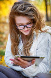 Young woman with a tablet sitting in the autumn park Stock Photography