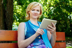 Young woman with tablet sitting on bench Royalty Free Stock Image
