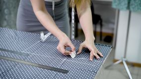 Young woman tailor drawing a pattern by piece of chalk on polka dots tissue. stock footage