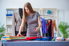 The young woman tailor working in workshop on new dress Royalty Free Stock Images