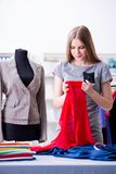 The young woman tailor working in workshop on new dress Royalty Free Stock Photo