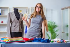 The young woman tailor working in workshop on new dress Royalty Free Stock Photos