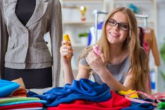 The young woman tailor working in workshop on new dress Stock Photography