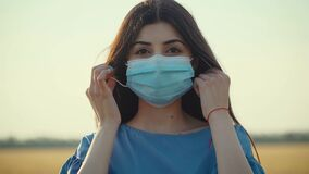 Young woman take off protective medical mask from face and smiling after coronavirus epidemic end