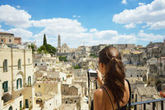 Young woman take photo with mirrorless camera to the old town of Matera. Beautiful traveller girl visit Sassi di Matera. Typical i royalty free stock image