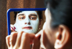 Young woman takes beauty mask in front of mirror Stock Photography