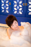 Young woman takes bubble bath Stock Images