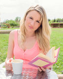 Young woman takes coffee and read a book on the terrace Stock Images