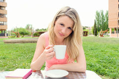 Young woman takes coffee at a terrace table Stock Images