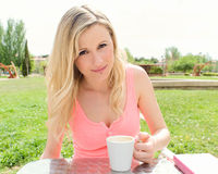 Young woman takes coffee at a terrace table Stock Photos