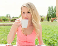 Young woman takes coffee at a terrace table Royalty Free Stock Photo