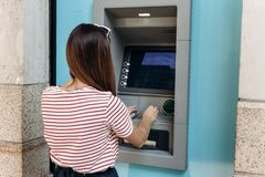 A young woman takes money from an ATM. Grabs a card from the ATM. Finance, credit card, withdrawal of money. stock photo