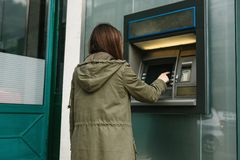 A young woman takes money from an ATM. Grabs a card from the ATM. Finance, credit card, withdrawal of money. The tourist withdraws money from the ATM for stock photos