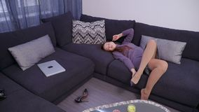 A young woman takes off her high-heeled shoes and lies down on the sofa