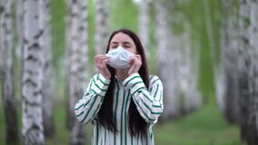 Young woman takes off medical mask and takes a deep breath in the birch grove